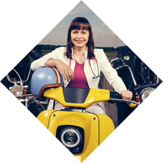 Landärztin sitzt auf einer gelben Schwalbe. Links und rechts von ihr zwei Biker.