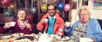 Landarzt mit drei alten Damen am Kaffetisch. Im Hintergrund festlich geschmückte Schrankwand und Luftballons.