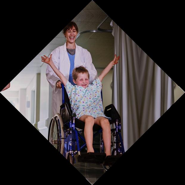 Zwei Kinder werden mit Rollstühlen über einen Krankenhausflur geschoben. Die Kinder strecken die Arme in die Luft und haben Spaß.